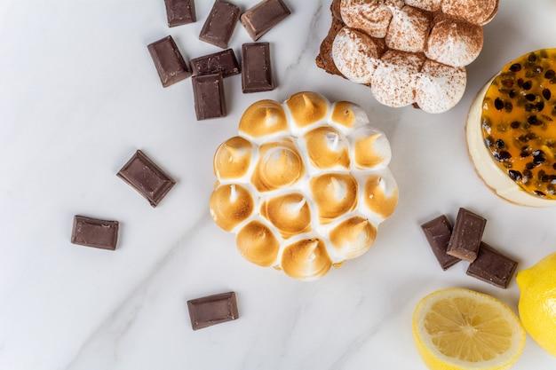 おいしいミニチョコレート、レモンパイ、パッションフルーツケーキのクローズアップ。コンセプトを調理します。