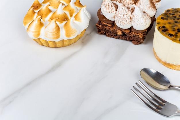 おいしいミニチョコレート、レモンパイ、パッションフルーツケーキのクローズアップ。クックのコンセプト。
