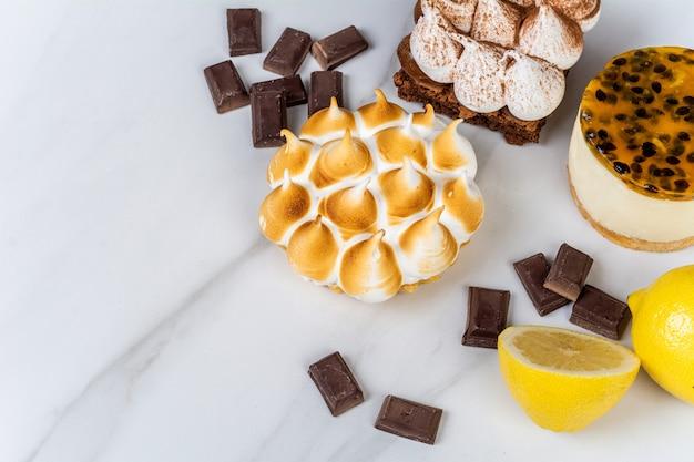 맛있는 미니 초콜릿, 레몬 파이 및 열정 과일 케이크에 근접합니다.