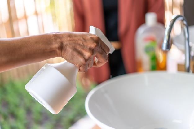 女性の手にクローズアップ。彼女は屋外の庭で洗面ときれいな流しのために白い噴霧器/霧を持っています