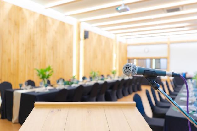 Крупным планом - микрофон у подиума с размытым длинным черным столом в теплом свете вольфрама.
