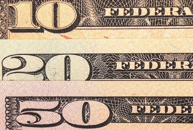 Крупным планом - банкноты доллара сша среднего достоинства, фото номиналом 10, 20 и 50 штук.