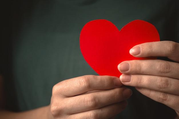 Крупным планом красное сердце в руках. женщина, держащая бумажное сердце на фоне груди