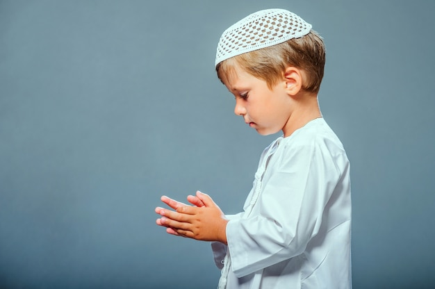 Close up on toddler dressed in white and praying