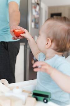 Заделывают малыша, держащего помидор