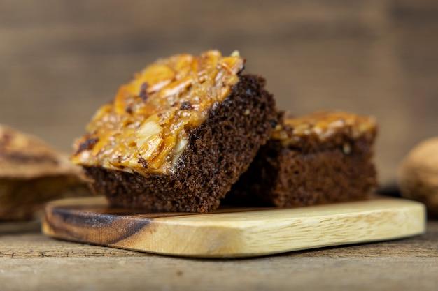 Закройте вверх по торту ириски на деревянном подносе и на стене деревянного стола.