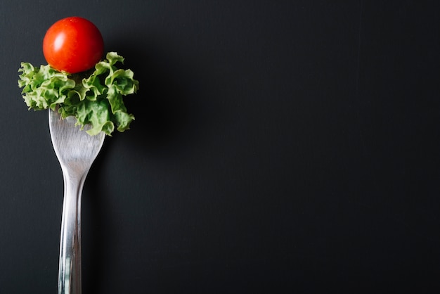 Close-up of tomato and lettuce with fork on black background