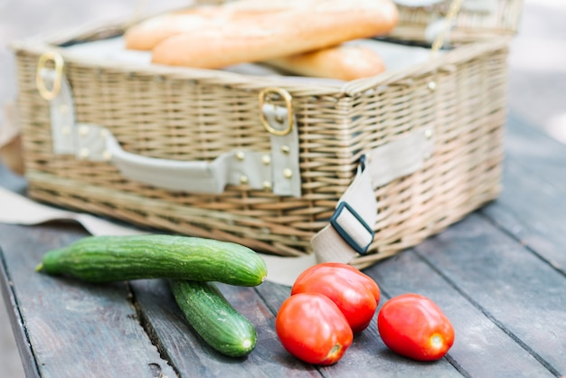 Close up of tomatoes and cucumbers over wooden table in front of an open picnic basket.