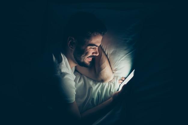 Крупный план сверху над высоким углом зрения портрет его симпатичного привлекательного веселого веселого парня, лежащего в постели с использованием сотового веб-сервиса, чата в сети ночью поздно вечером дома темная освещенная комната дом