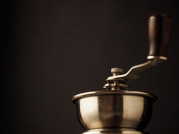 Верхняя часть конца-вверх винтажной ручки мельницы кофемолки на темной предпосылке.