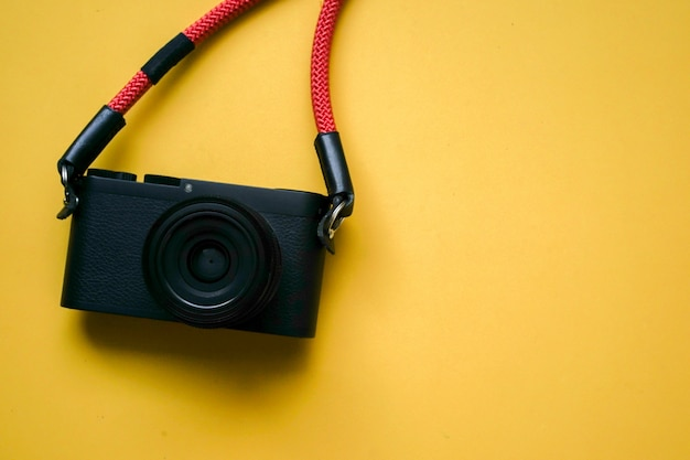 Close up top view of black camera with red strap and copyspace