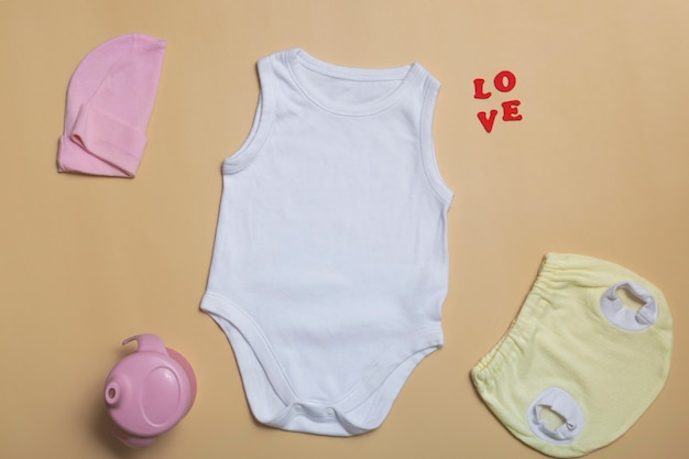 Close-up top view. blank white bodysuit mockup, yellow newborn panties on beige background, with copy space - perfect baby clothes mockup template