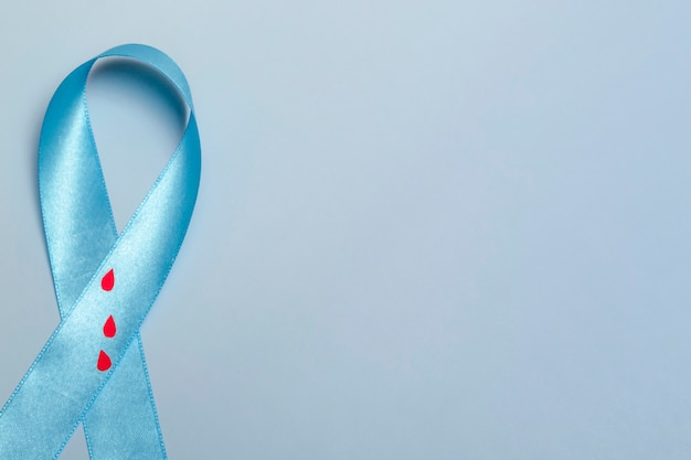 Close up top view of concept for world diabetes day 14 november. blue ribbon with drops of blood on a blue background.
