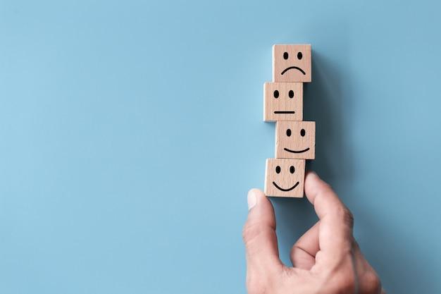 Крупным планом вид сверху рука клиента выбирает смайлик на деревянном кубе