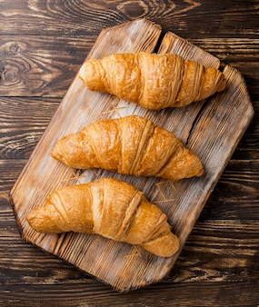 Close-up top view delicious baked croissants on wooden board