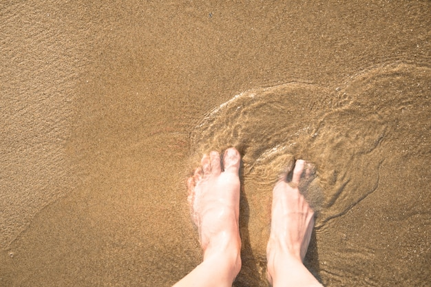 Close-up top view of feet in wet sand