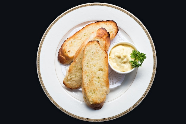 Close up top view garlic  bread baked sliced with mayonnaise and parsley on white plate