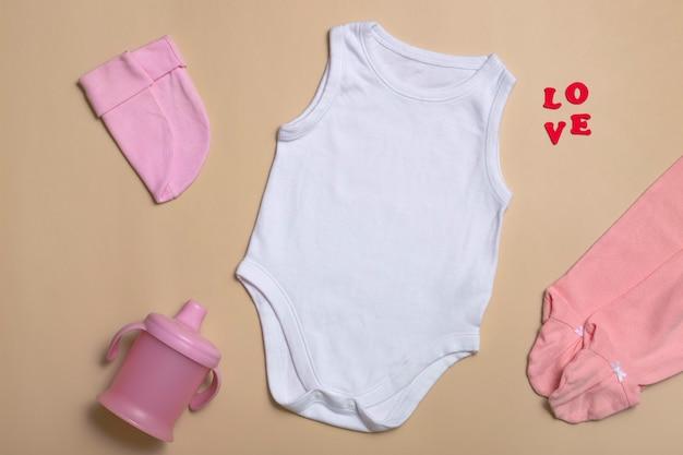 クローズアップ上面図。モックアップブランクピンクのボディスーツ、ピンクのパンツ、ベージュの背景の新生児用の帽子とカップ、コピースペース付き-ベビー服の完璧なモックアップテンプレート