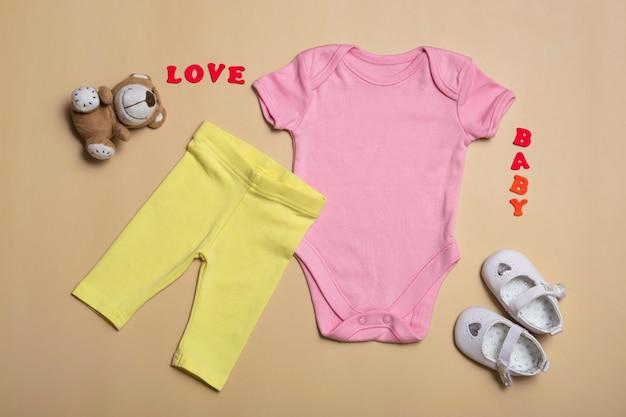 Крупным планом вид сверху. мокап пустого розового боди, желтых брюк и белых сандалий для новорожденных на бежевом фоне, с копией пространства - идеальный шаблон мокапа детской одежды