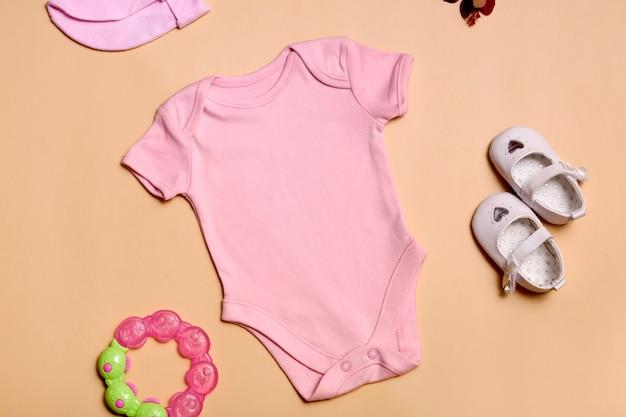 Крупным планом вид сверху. макет пустого розового боди для новорожденных для девочки на бежевом фоне, с копией пространства - идеальный шаблон макета детской одежды