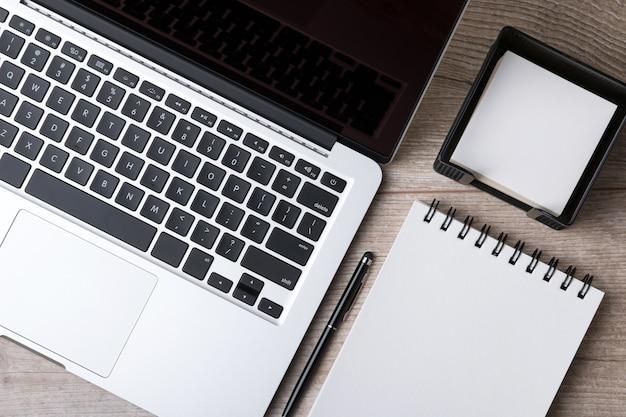 ビジネスマンの職場のクローズアップ上面図。ノートパソコン、ノートブック、ペン