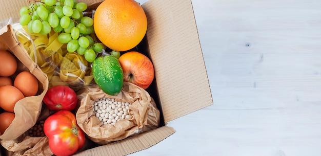 ファーマーズマーケットからの果物野菜豆卵でいっぱいの段ボール箱の上面図をクローズアップ