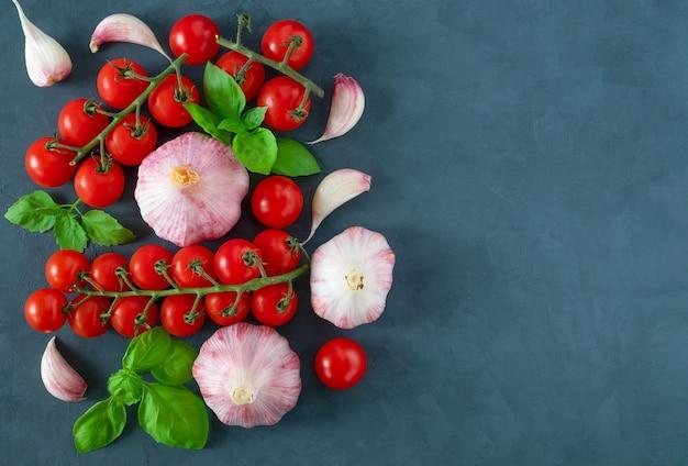 料理の材料としてのチェリートマト、ニンニク、新鮮なバジルの葉のクローズアップ上面図。