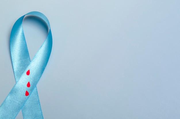 11월 14일 세계 당뇨병의 날에 대한 개념의 상위 뷰를 닫습니다. 파란색 배경에 혈액 방울이 있는 파란색 리본.