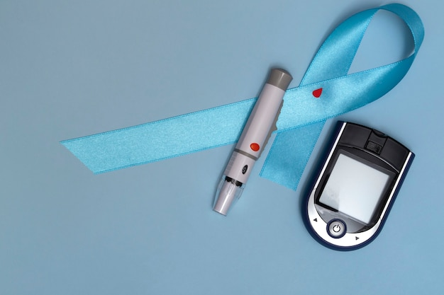 11월 14일 세계 당뇨병의 날에 대한 개념의 상위 뷰를 닫습니다. 파란색 배경에 혈액 방울과 글루코미터가 있는 파란색 테이프.