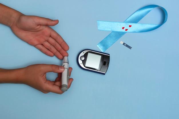 11월 14일 세계 당뇨병의 날에 대한 개념의 상위 뷰를 닫습니다. 아이는 파란색 배경에 혈당을 측정하고 혈액 방울이 있는 파란색 리본을 측정합니다.