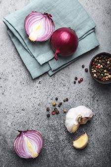 素朴な灰色の石の背景にカット生の新鮮な赤玉ねぎ、ニンニク、調味料のクローズアップ、上面図。料理、ベジタリアン料理または健康的な食事の概念、きれいな有機食品