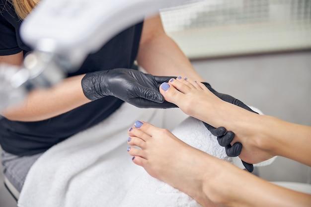 つま先の爪をペイントした後、ネイリストによってマッサージされている女性の足の上面図をクローズアップ