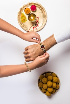 ラクシャバンダンフェスティバルで白い背景に分離された彼女の兄弟の手にカラフルなラキを結ぶ女性の手の上面図をクローズアップ