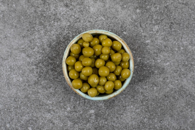 확대. 회색 표면 위에 그릇에 있는 녹색 통조림 완두콩의 상위 뷰