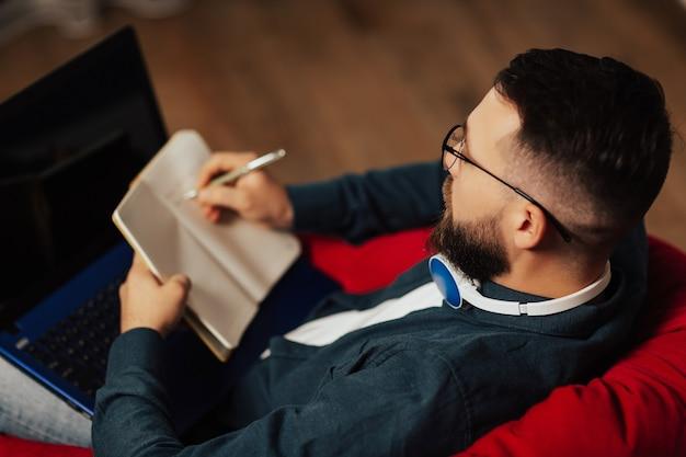 ラップトップで作業している男性のクローズアップ上面図とノートブックにメモを取ります。フリーランサーは自宅で働いています。オンラインマーケティング、成人向けの教育。