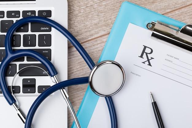 Крупным планом вид сверху рабочего места врача. стетоскоп, компьтер-книжка и бланк рецепта на деревянной поверхности.