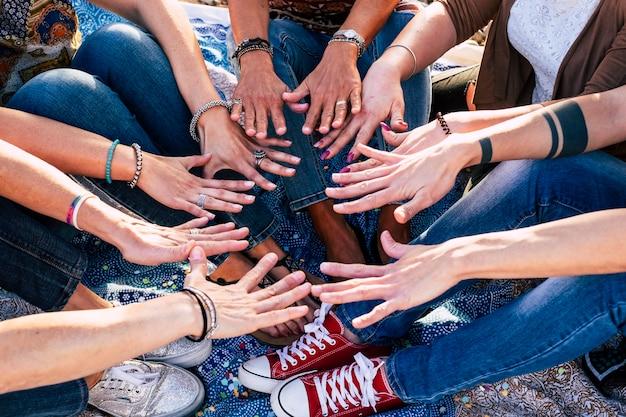 手を合わせている人々の上面図をクローズアップします。団結とチームワークを示す手のスタックを持つ友人-友情の白人の人々-流行に敏感なカジュアルスタイル-多様性の年齢