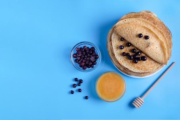 Крупным планом вид сверху русской национальной кухни и десертные блины с ягодами и медом. традиционное блюдо на масленицу. выборочный фокус. скопируйте пространство.