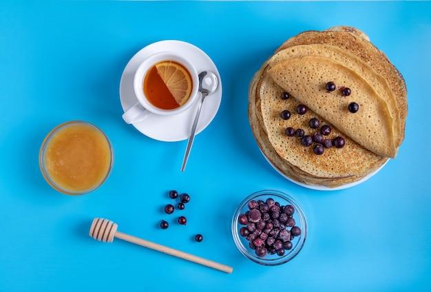Крупным планом вид сверху русской национальной кухни и десертные блины с ягодами и медом. традиционное блюдо на масленицу. выборочный фокус.