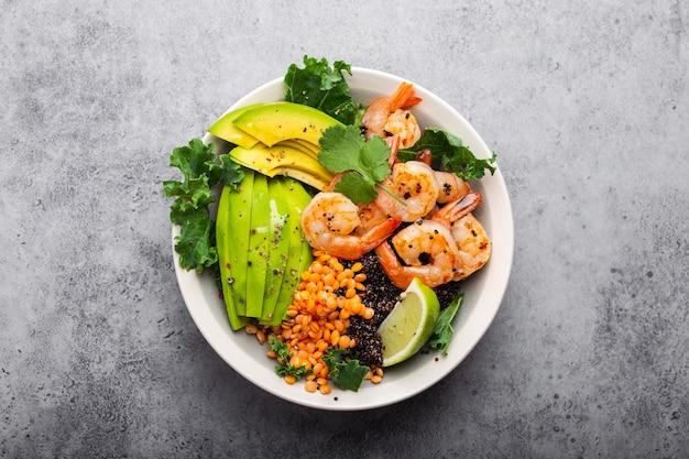 Крупным планом, вид сверху салатник с креветками, авокадо, свежей капустой, киноа, красной чечевицей, лаймом и оливковым маслом на сером каменном фоне. чаша для обеда, здоровое и чистое питание, диета или концепция питания