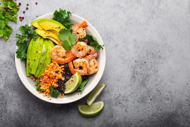 Крупным планом, вид сверху салатник с креветками, авокадо, свежей капустой, киноа, красной чечевицей, лаймом и оливковым маслом на сером каменном фоне с пространством для текста. обеденная тарелка для здорового питания или диеты