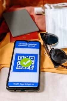 Крупным планом вид сверху смартфона с иммунным цифровым паспортом здоровья и чемоданом с одеждой и защитными масками. отрицательный тест на вирус - covid-19. вертикальный. концепция нового нормального.