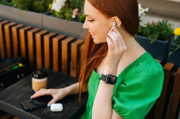 무선 이어폰을 만지고 웃고 있는 젊은 여성, 테이블에 앉아 휴대폰으로 음악 듣기, 여름날 야외 카페 테라스, 흐린 배경, 선택적 초점