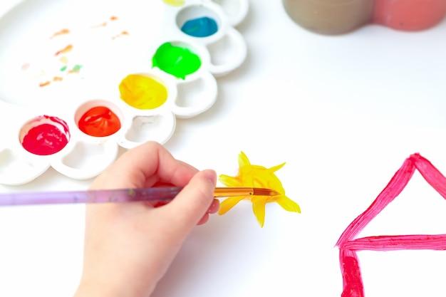 Крупным планом вид сверху руки ребенка с кистью, рисующей солнце над домом на белой бумаге.