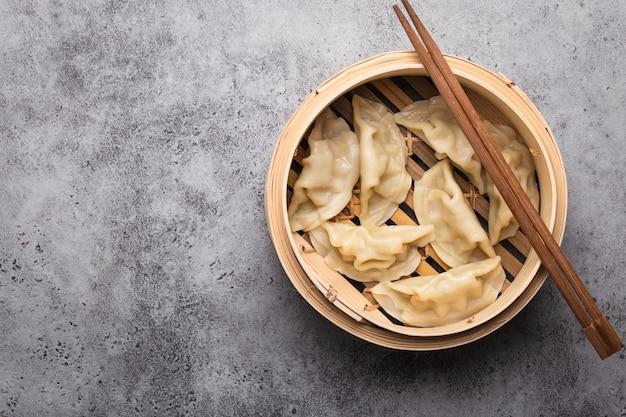 テキスト用のスペースと灰色の素朴な石の背景に箸で竹蒸し餃子の伝統的なアジア/中国の餃子のクローズアップ、上面図。本格的な中華料理、コピースペース