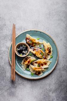 灰色の素朴な石の背景に醤油と箸で青いプレートの伝統的なアジア/中国の餃子のクローズアップ、上面図。本格的な中華料理