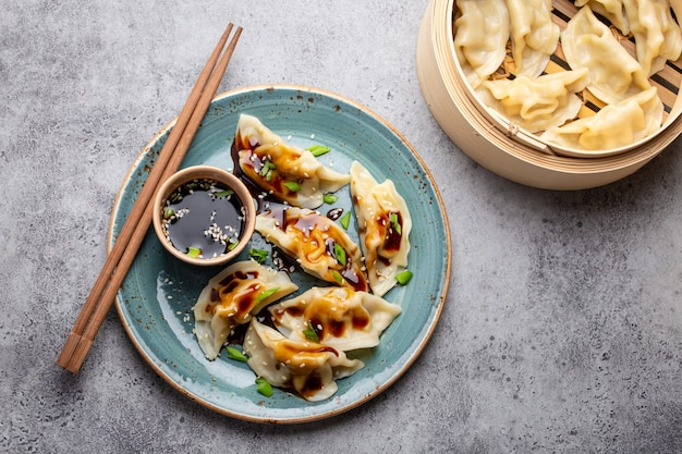 灰色の素朴な石の背景に醤油、箸、竹蒸し器で青いプレートの伝統的なアジア/中国の餃子のクローズアップ、上面図。本格的な中華料理