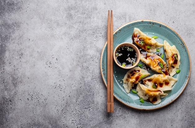 醤油とテキストのためのスペースと灰色の素朴な石の背景に箸と青いプレート上の伝統的なアジア/中国の餃子のクローズアップ、上面図。本格的な中華料理、コピースペース