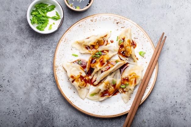 灰色の素朴な石の背景に醤油と箸と白いプレート上の伝統的なアジア/中国の餃子のクローズアップ、上面図。本格的な中華料理