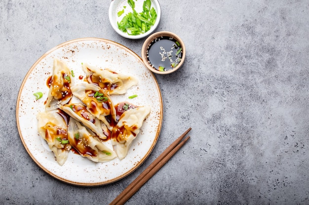 醤油とテキストのためのスペースと灰色の素朴な石の背景に箸と白いプレート上の伝統的なアジア/中国の餃子のクローズアップ、上面図。本格的な中華料理、コピースペース